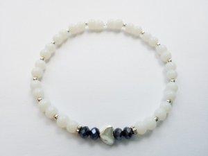 Perlenarmband mit weißen Perlen, silberfarbenem Herz, das von dunkelblauen Perlen flankiert wird
