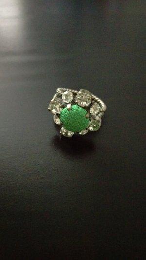 Ring von Konplott mit grünem Stoff und klaren Steinen