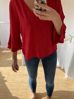 Rote Bluse mit Glockenärmeln