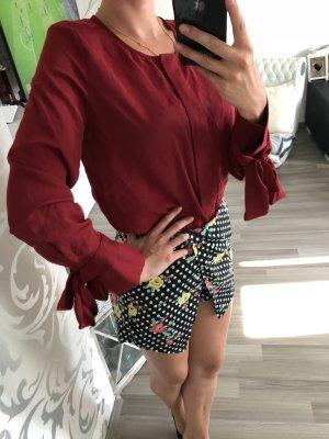 Rote Bluse mit Schleifen an den Ärmeln