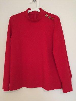 Rote Bluse mit Schmuckdetails