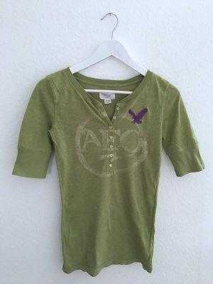 Schönes grünes Henley-Shirt mit 3/4-Arm und lila Stick