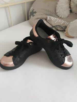 Schwarze Adidas Schuhe mit Gold.