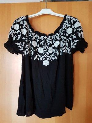 schwarze Bluse mit floraler, weißer Stickerei