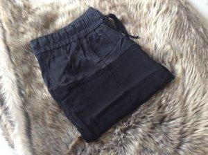 Schwarze Bundfaltenhose mit satinierten Details