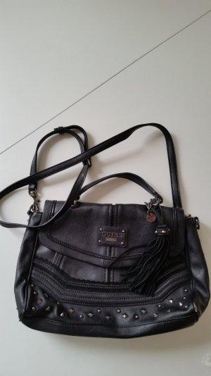 Schwarze Guess Tasche mit Nieten und Quastendetail. Abnehmbarer langer Henkel.