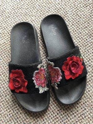 Schwarze Pantoletten mit Blütendetail