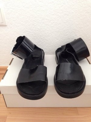 schwarze Sandalen mit großer Fuß-Schnalle
