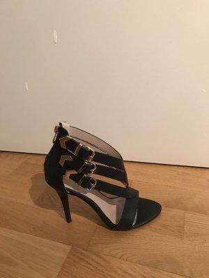 Schwarze Sandaletten mit goldenen Schnallen