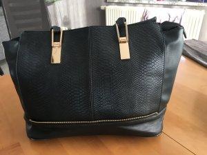Schwarze Tasche mit goldenen Applikationen