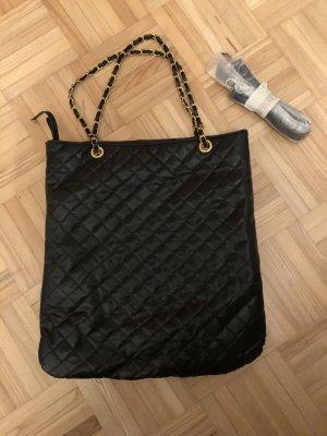 schwarze Tasche mit goldenen Kettenhenkel
