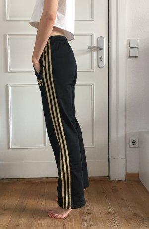 schwarze Trainingshose mit goldenen Streifen
