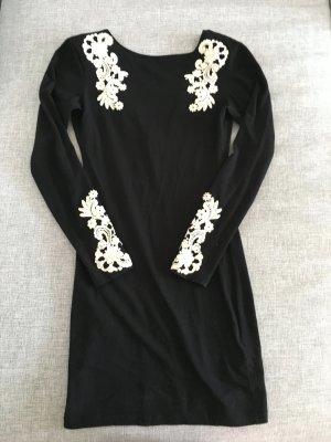 Schwarzes Kleid mit weißen Applikationen
