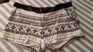 Shorts mit Ethnoprint. Schwarzer, metallisch glänzender Bund.
