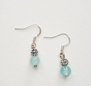silberfarbene Ohrringe mit silberfarbenem Blume und türkisfarbener Perle