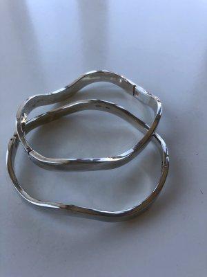 Silberne Armreifen in Wellenform