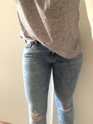 Skinny-Jeans mit Knieschlitzen.
