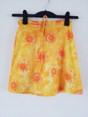 sonnengelber Wickelrock mit orangefarbenen Blumen