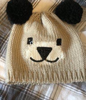 Süße Mütze mit schwarzen Bommeln als Ohren