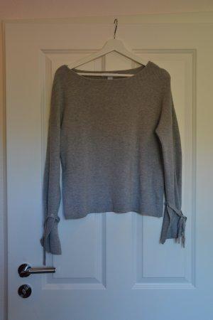 Süßer grauer Pullover mit Schleifen an den Ärmeln