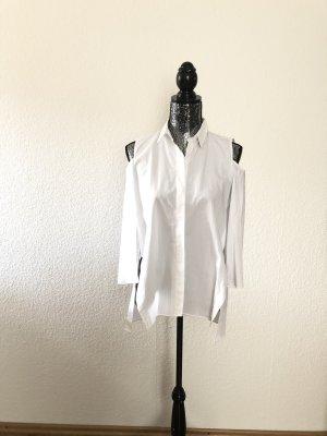 Weiße Bluse mit Aussparungen an den Schultern.