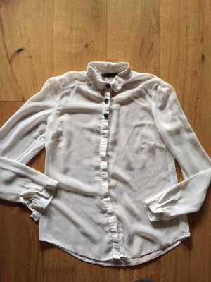 Weisse Bluse mit karierten Knöpfen und goldenen Details