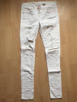 weiße Hose mit vielen Löchern
