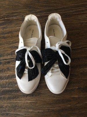 Weiße Sneaker mit Schleife