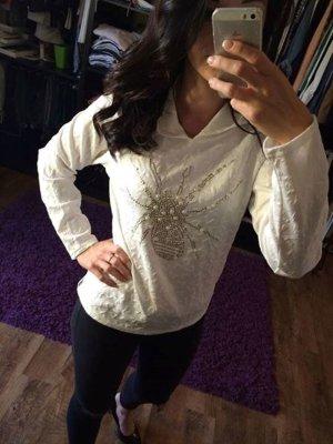 weißer Pullover mit goldenen Details