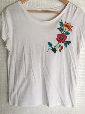 Weißes T-Shirt mit Blüten Stickereien.
