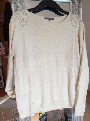 Wollweißer dünner Pullover mit silbernen Applikationen auf der Schulter