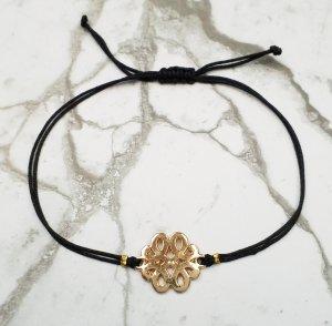 Complemento para los brazos negro-color oro