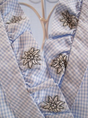 Zauberhaft schöne hellblaue Vichykarobluse mit Rüschen am Kragen, verziert mit Edelweiß und herzförmigen Manschettenknöpfen im Holzlook