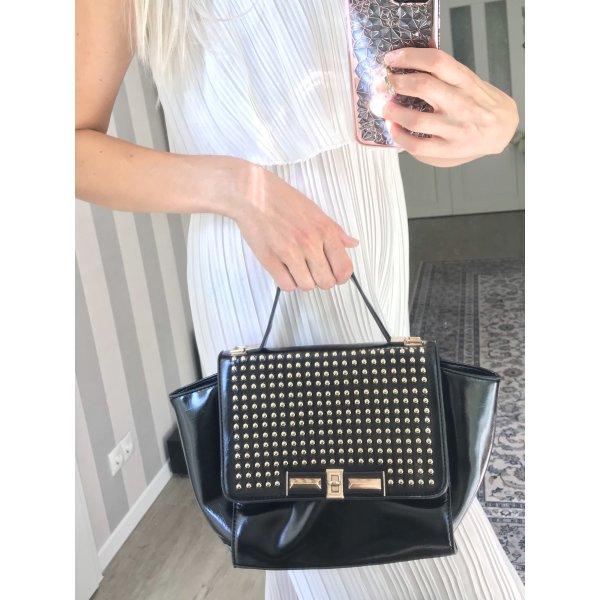 Modische schwarze Handtasche mit Nieten in gold